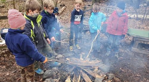 Kinder spielen am Lagerfeuer
