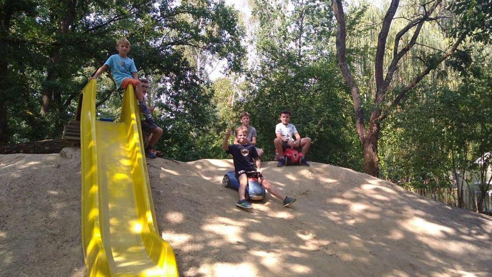 Kinder mit Bobbycars am Lehmhang und an der Rutsche