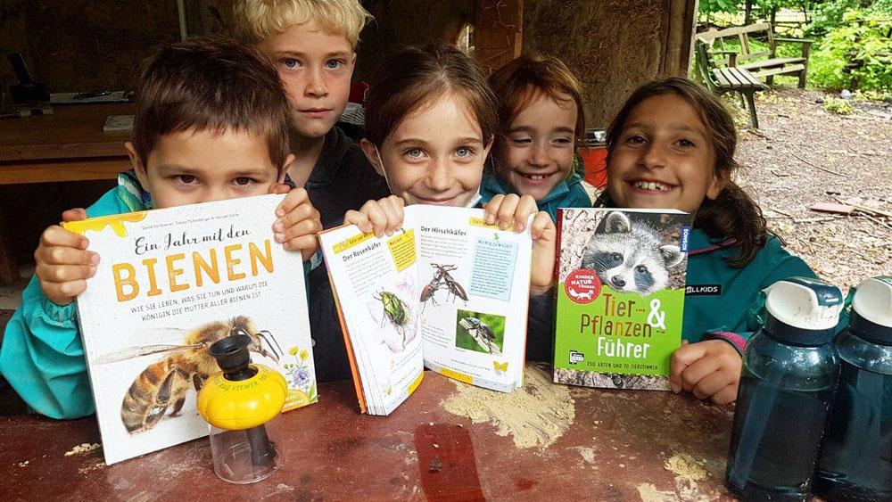 Fünf Kinder halten die neuen Bestimmungsbücher hoch