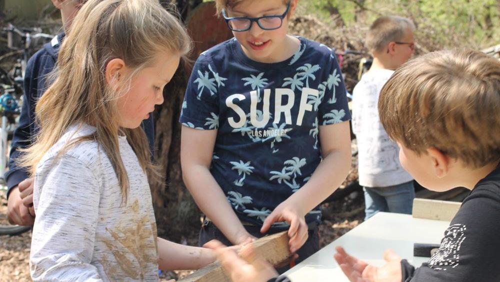 Drei Kinder arbeiten mit einem Holzbalken