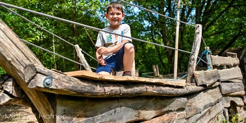 Junge sitzt lachend auf Piratenschiff